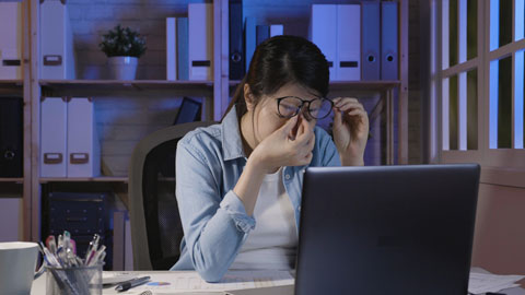 Female rubbing eyes while looking at computer