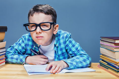 Young boy squinting while reading